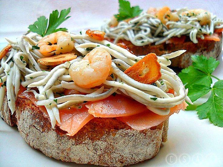 Tosta de salmón ahumado con gulas y gambas al ajil...