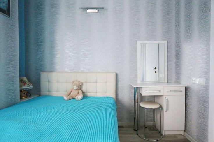 Маленькая спальня. Два типа освещения: общее и над кроватью. Кровать с мягким изголовьем 120 см в ширину. Подходит для одного или двух взрослых, а также детей. Слева от кровати тумбочка с секретом. Туалетный столик справа.