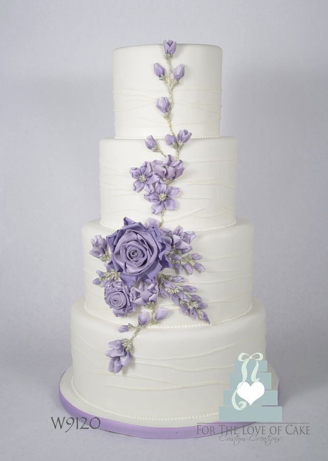This 4 tier white fondant covered wedding cake has edible ribbon-like flowers cascading down the front in a delicate lavender tone.