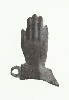 Pilgrim badge Badge in the shape of a hand with a beaded cuff and a small loop at the top. There is a pin on the back. It is possible that this is a pilgrim souvenir, but if so, the shrine where it was made is unknown. Pilgrims who travelled to religious shrines frequently bought souvenirs of their pious journey such as ampullae (small bottles for holy water), badges and figurines.  Production Date: Late Medieval; 14th century