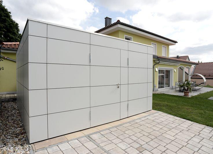 Gartenhaus und Geraetehaus im modernen Design in Form eines Kubus verkleidet mit Fassadentafeln HPL in grau