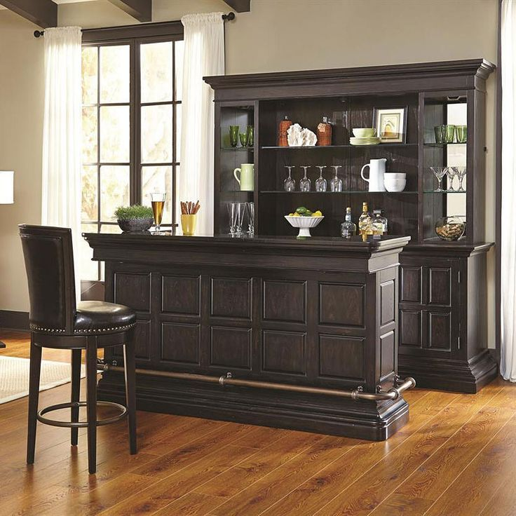 Sophisticated and elegant, this Burton Home Bar Set by Pulaski Furniture will provide the look and style you want in your home. Your eyes will be drawn to an antique brass finished foot rail and a laminated black granite top. While making drinks, entertain your guests with the wireless connect speaker system and easily prep with the pull-out cutting board and a stainless steel dry sink. The bar has all the right storage features including an utensil tray with a felt bottom, stemware holders…