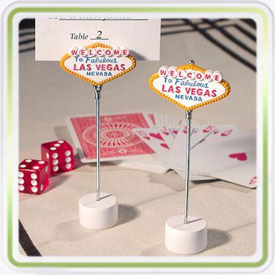 """Marcador de Puesto - Viva Las Vegas! Para una fiesta temática de juegos de azar, naipes y muchas monedas... de chocolate, este tarjetero de Las Vegas será el toque ideal para tu evento. Su base circular está elaborada en acero inoxidabe y el alambre de metal que termina con un clip que sirve para insertar una tarjeta de agradecimiento, de ubicación de puestos o una foto, termina con un divertido letrero que dice """"Welcome to fabelous Las Vegas Nevada"""", este letrero está elaborado en resina."""