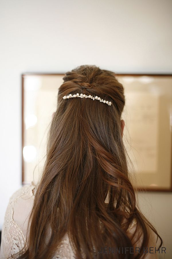 For a simple classic wedding headpiece to wear in your long, curly bridal hair, the Jennifer Behr simple Pearl Comb is your best bet. It stands out in a half up, half down curly look and will also look great pinned into your wedding veil.