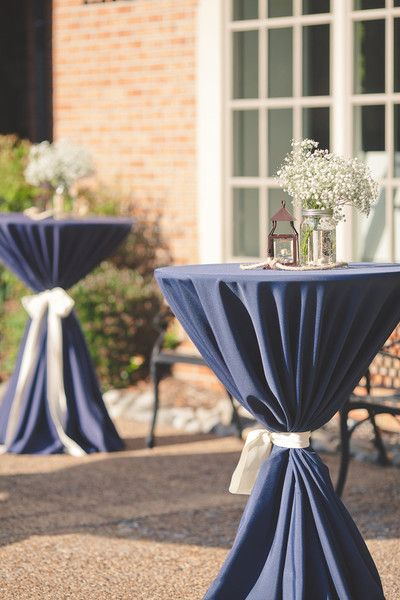 A vintage-chic cocktail hour with navy blue high-top tables, lanterns and baby's breath arrangements {@bitofivory}