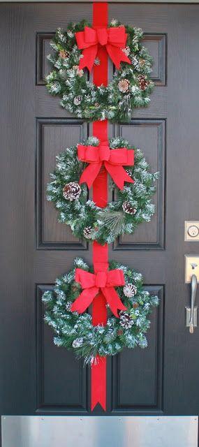 Puerta decorada con tres coronas de navidad en forma vertical. #DecoracionNavidad