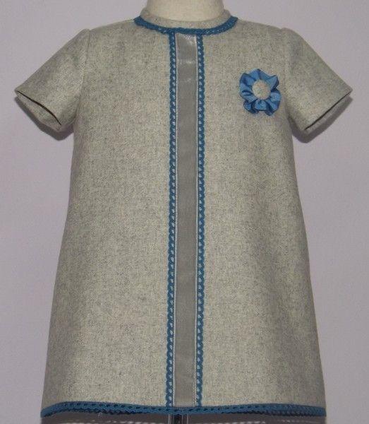 Vestido para bebe niña en paño gris adornado con lazo de terciopelo gris y punto de ojal azul azafata. Flor a juego. Forrado.
