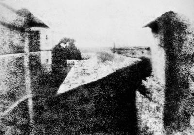 """1826 - A PRIMEIRA FOTOGRAFIA DO MUNDO: tirada no verão de 1826, na França, da janela da casa de Joseph-Nicéphore Niepce, encontra-se preservada até hoje. Trata-se de uma imagem produzida numa placa de estanho coberta com um derivado fotossensível de petróleo, chamado Betume da Judéia. Nièpce chamou o processo de """"heliografia"""", gravura com a luz do Sol. Foram exigidas cerca de oito horas de exposição à luz solar."""