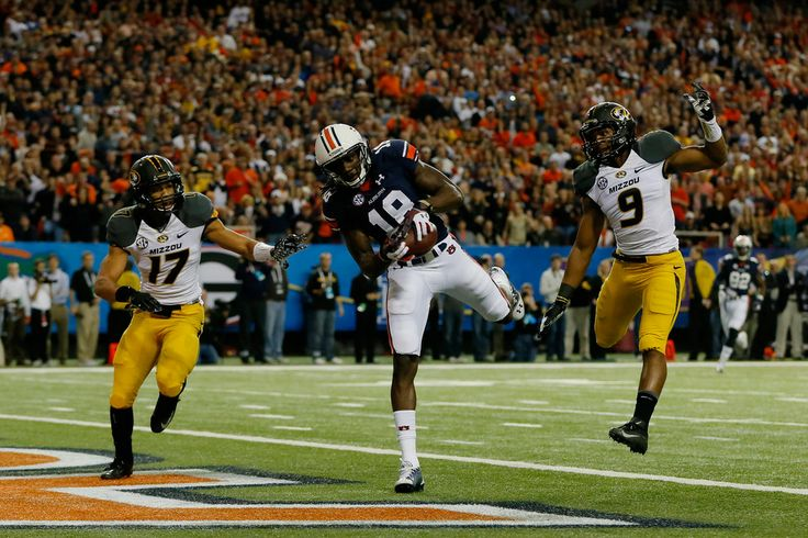 Sammie Coates #18 of the Auburn Tigers scores a touchdown against Matt White #17 and Braylon Webb #9 of the Missouri Tigers in the first quarter during the SEC Championship Game at Georgia Dome on December 7, 2013 in Atlanta, Georgia.