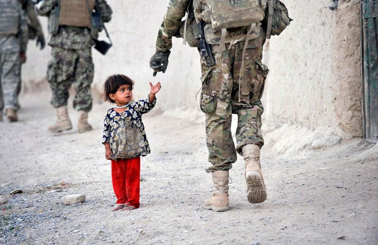 An Afghan girl greets a joint patrol of US troops from the Charlie Company, 2-87 Infantry, 3rd Brigade Combat Team and Afghan National Army soldiers at Kandalay village in the southern Afghan province of Kandahar,