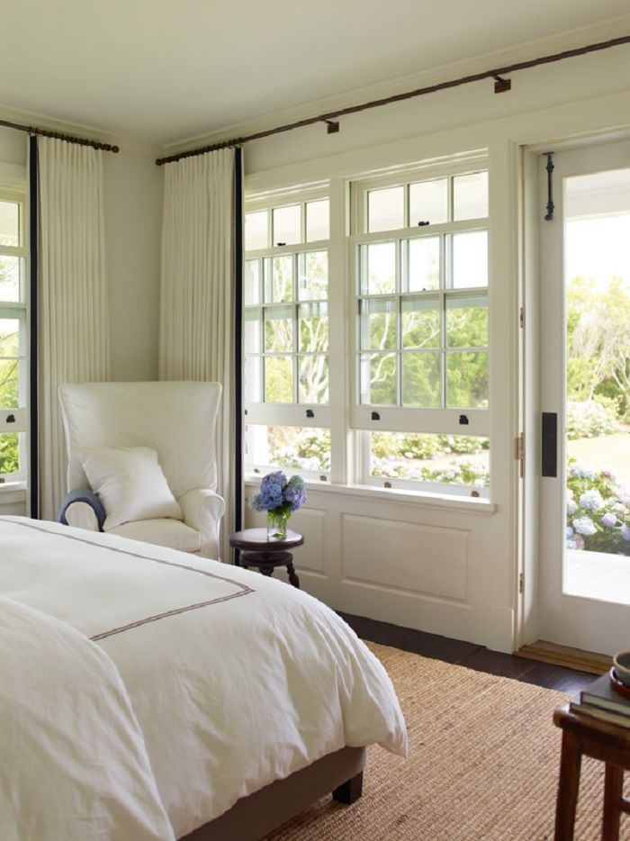 Huge windows let the outdoors in, providing the perfect scenic decor for the bright bedroom of this beach house.