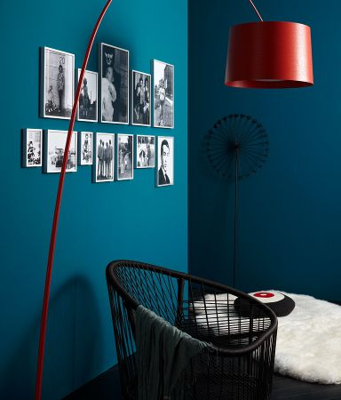 Love how they have hanged the photographs and LOVE the red lamp on the blue wall!