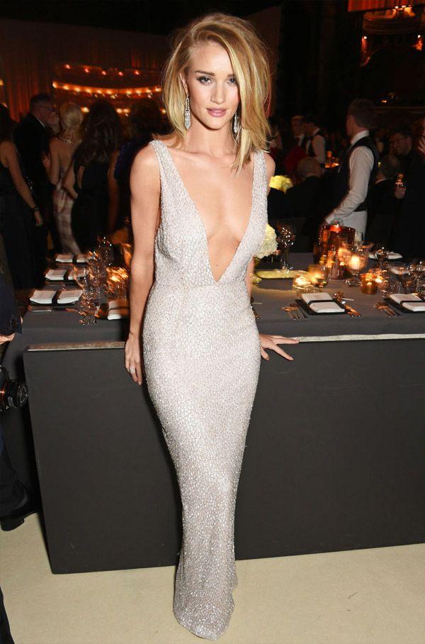 Look da modelo Rosie Huntington-Whitely usando vestido prateado com super decote.