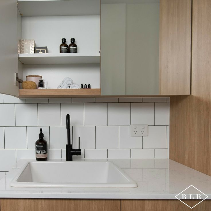 Red Lily Renovations Bathroom - Perth. Ultra white gloss wall tile in brickbond pattern. Essa Stone Verona bench top. Elegant Oak laminex doors.