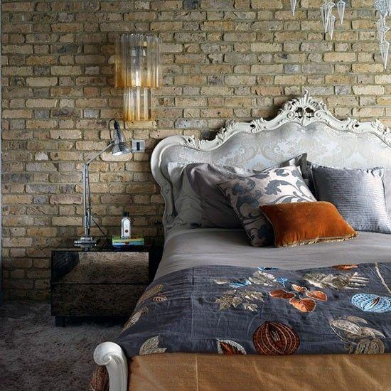 Кровать с стиле барокко резко контрастирует с кирпичной стеной. .