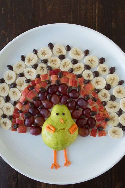 Crear un plato de fruta saludable de acción de gracias en la forma de un pavo usando una pera, uvas, manzanas, plátanos y uvas pasas cubiertas de chocolate!