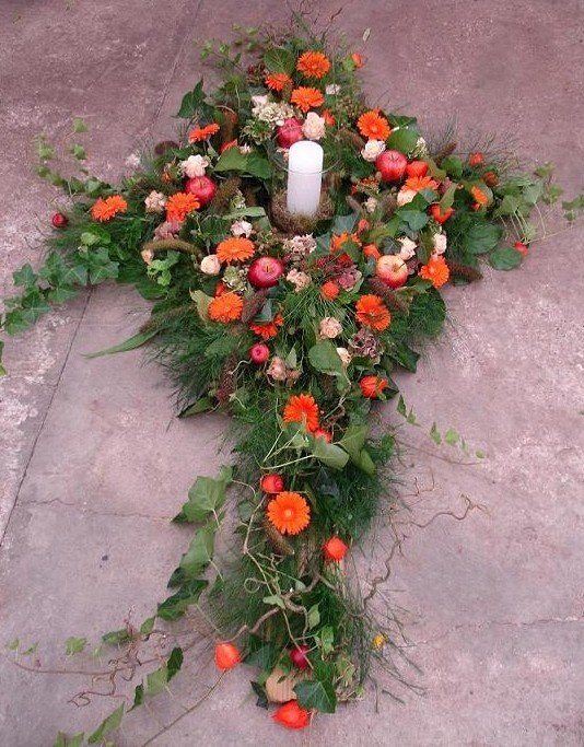 Cross shaped arrangement that adorns the complete coffin.  With candle  By BloemenVanMadeleine
