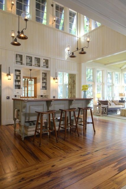 An open, light, and airy rustic kitchen with painted beadboard walls, wood floors, and clerestory windows