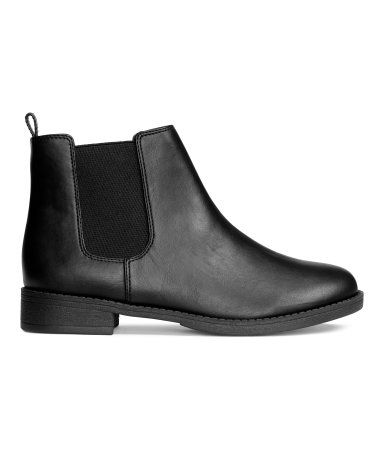 Black. Chelsea boots in imitation leather with elasticized panels at sides and…