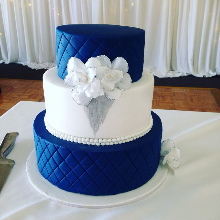Royal blue quilted cake with a hint of silver & white wafer roses.