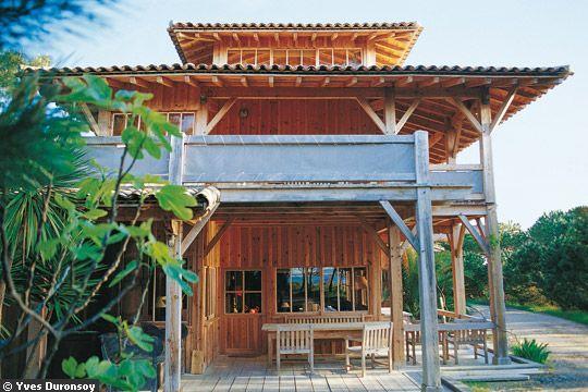 Une maison en bois avec de multiples terrasses