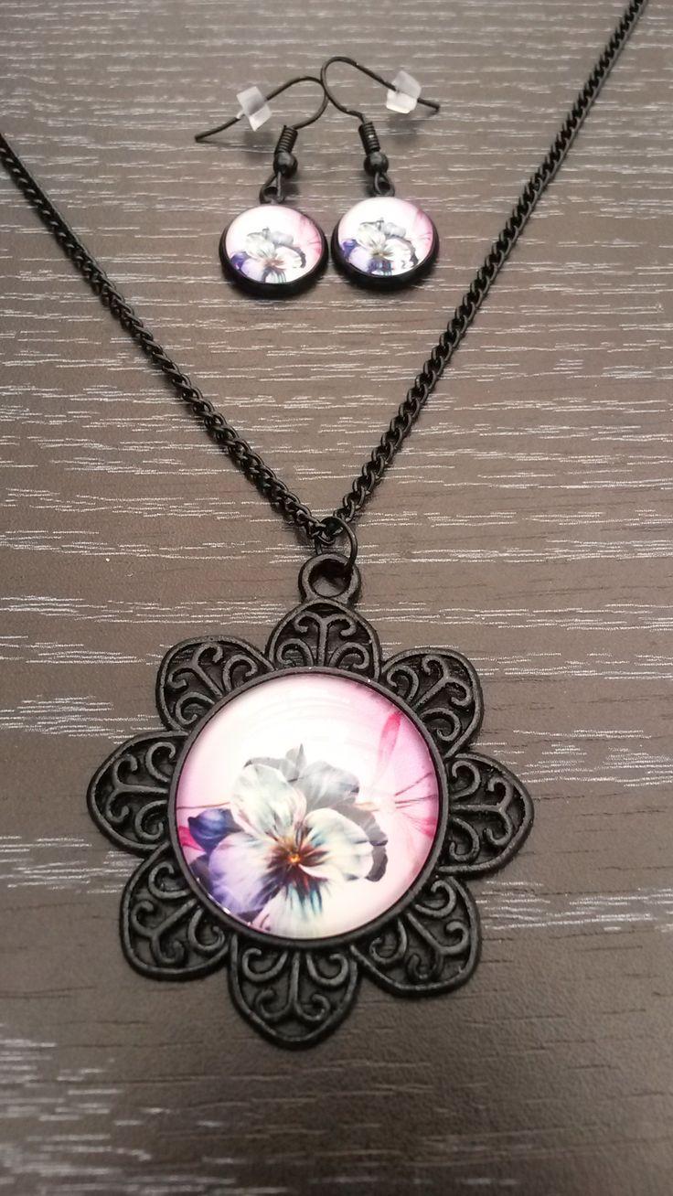 Zwarte halsketting met bloem medaillon en viooltje. Met bijpassende oorbelletjes.