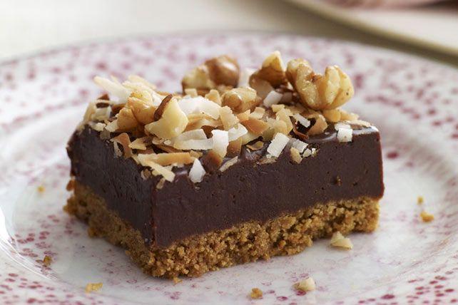 Du fudge chaud maison est versé sur une croûte de biscuits graham, garni de noix et de noix de coco grillée, puis réfrigéré pour donner des barres riches, sans cuisson au four.
