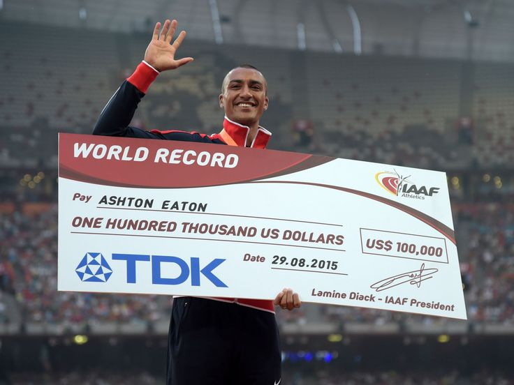 Ashton Eaton (USA) poses with the gold medal and $100,000 check after winning the decathlon with a world record 9,045 points.  Kirby Lee, USA TODAY Sports