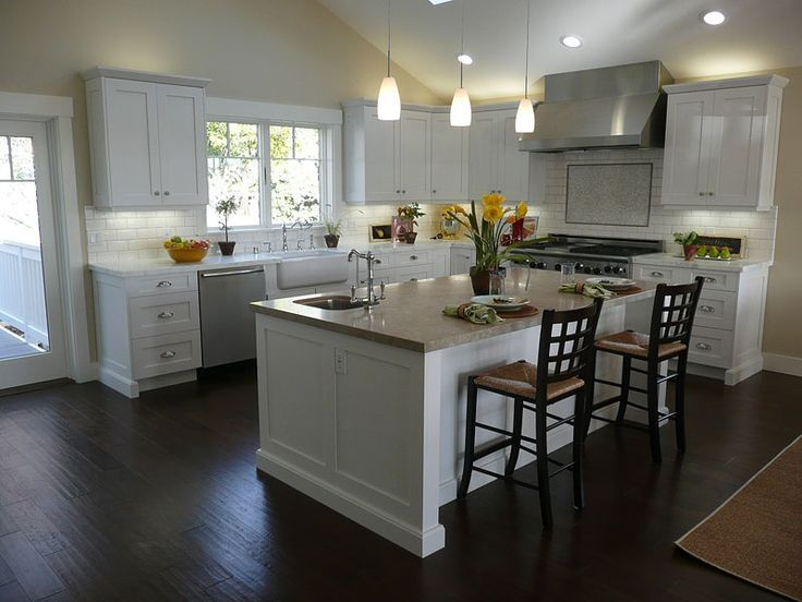 great kitchen in white with dark brown floor and plenty of light