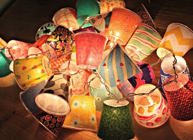 Maak je eigen lichtslinger. Je gebruikt je favoriete stofjes, plastic bekertjes en knutselen maar.http://lifedsign.com/2012/06/lampen-kapjes-aan-een-lichtslinger/