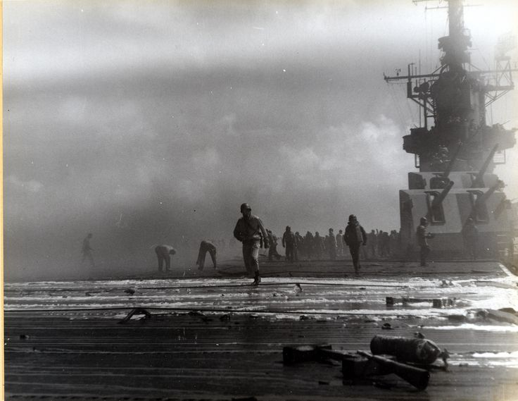 Sailors fight fires on board a battle-damaged Intrepid (CV 11). This image is part of a photograph album detailing the wartime service of the carrier Intrepid (CV-11) in the Pacific during World War...