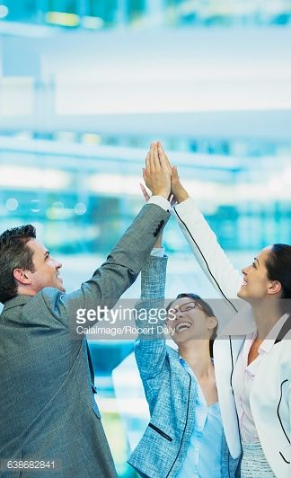 Enthusiastic business people with arms raised in office : Stock-Foto