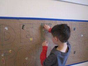 añadiendo Pegatinas Para El mural de la comparación del alfabeto