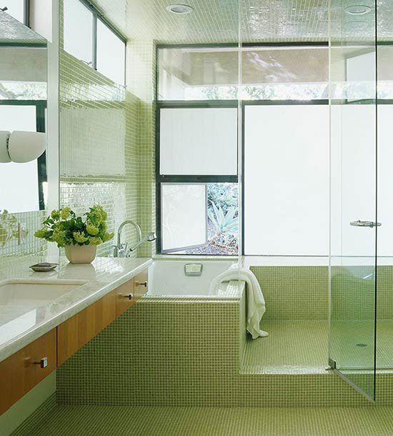Two-in-One This spacious bathroom has both the bathtub and shower enclosed in one space. The shower, on the right, has plenty of room for more than one person, and the large soaking tub is on the left. Clean, geometric lines and small green tiles give the bathroom a sophisticated and modern look.
