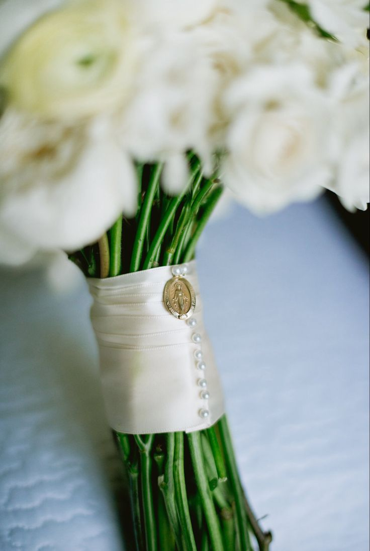 """Bridal bouquet wrapped in doubleface cream satin ribbon fashioned with pearl head pins. The miraculous medal, a beautiful heirloom from the brides grandmother,is pinned to the ribbon for """"something old""""."""