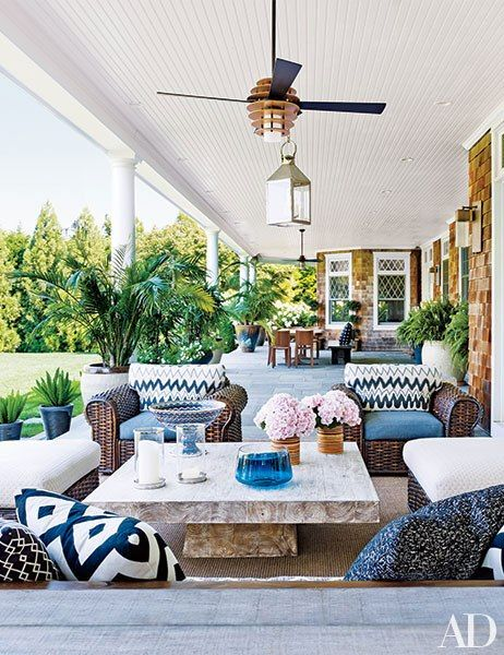The rear porch of this Southampton, New York, home designed by Juan Montoya features wicker seating and an Andrianna Shamaris teak cocktail table.