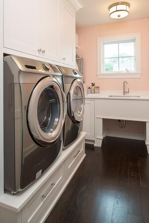 White and pink laundry room features a built-in washer and dryer riser platform fitted with drawers with cabinets above.