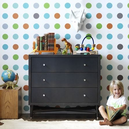The solid, dark color of this dresser helps anchor the room against the bright polka dots!