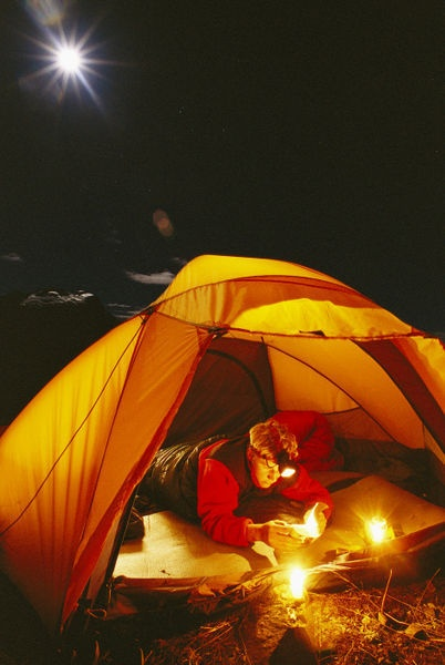 'Man reading in tent at night with Cerro Victoria in distance.' by National Geographic on artflakes.com as poster or art print $16.63