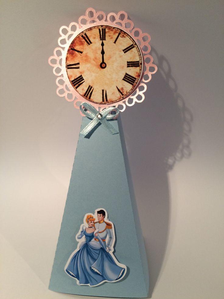 Caixinha triangular feita em papel 180gr, decorada com apliques de relógio e da Cinderela. <br>Ideal para decorar e colocar lembrancinhas. <br> <br>* Para não correr o risco de soltar a tampa é necessário colocar uma fita adesiva na parte de trás. <br> <br>Pode ser usado como centro de mesa. <br>Medidas: 17cm alt x6prof x 6 larg