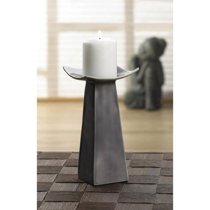 The curved edges of the candle platform give the geometric structure of this tall candle holder a marvelously modern twist. Made with aluminum and finished with a neutral gray glaze, it will stand as a testament to your great design taste. Candle not included.