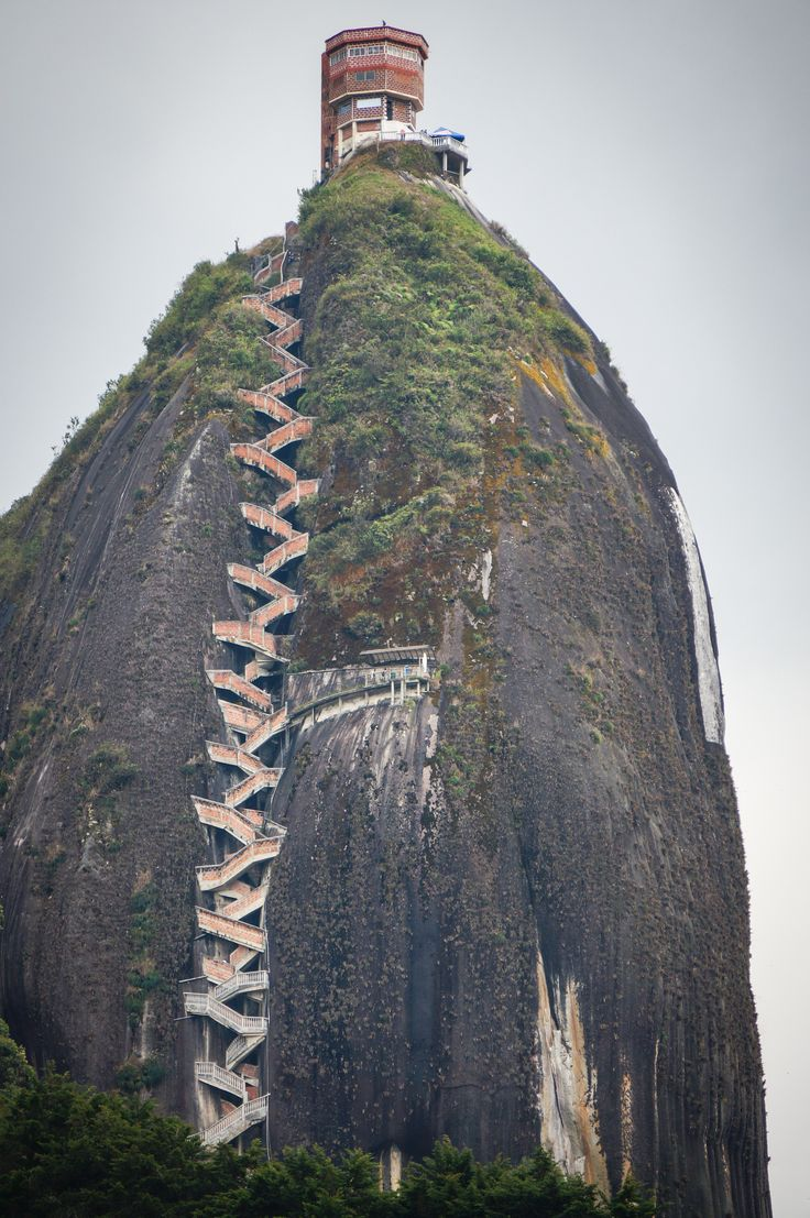 Guatape Rock in Colombia ~~ The rock, which is almost entirely smooth with one long crack running top to bottom on one of the faces.  Across this crack, is wedged a 649-step masonry staircase, that appears like a giant stitch holding the split rock together.