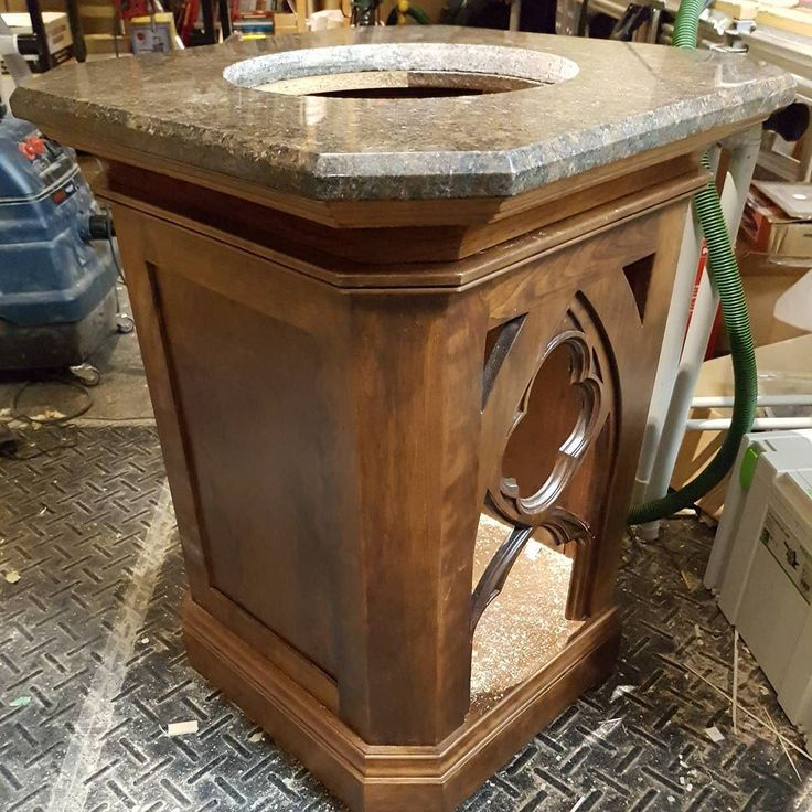 This walnut and granite topped baptismal font was originally made by an inmate in a prison and donated to the church. Unfortunately it was a little too tall to be used. I was asked by our priest to cut the hieght down so he could actually use it without bumping the babies head on the stone. After shortening the column the arch suffers a little in terms of proportion but everything else seems to work.  #oakvillecabinetry #baptismalfont #charity #talentsforcharity #giftsfromgod #walnut #church…