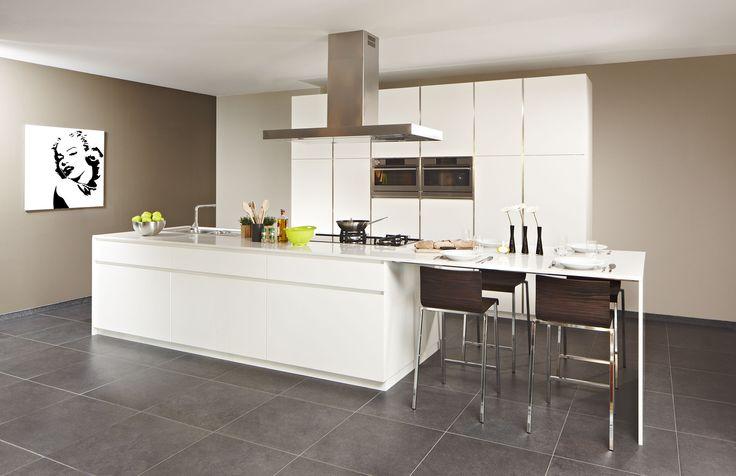 Moderne opstelling van de keuken waarvan het werkblad naadloos OVERloopt tot tafel. Door de totaal witte uitvoering bekomen we een strak design.