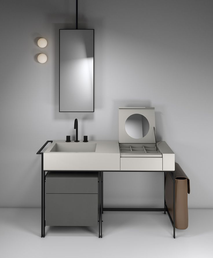 """NARCISO bathroom collection by CIELO, made up of large ceramic washbasin with a large basin and a convenient top combined with a """"vanity"""" section, including mirror and compartments. All items are in the Pumice finish. The vanity is set within an elegant asymmetrical structure in matte black steel. The drawer unit is in the Cemento finish and the laundry bag on the side is in natural leather. Argo is the ceiling-mounted mirror. Design by Parisio and Pezzano #ceramic #bathroomdesign"""