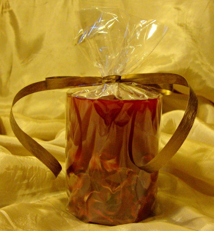 Κόκκινο μικρό στρογγυλό κερί με αποξηραμένα λουλούδια και άρωμα αχλάδι στη συσκευασία του.