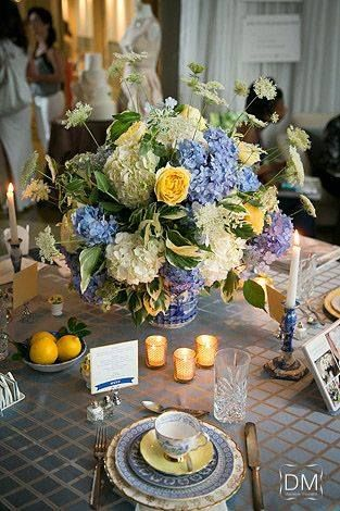 This beautiful arrangement features yellow garden roses, white hydrangea, blue hydrangea, Queen Anne's lace, and greenery. The table was scattered with gold lattice votives, a bowl of lemons, vintage china, and candlesticks. The event took place at The Greystone at Piedmont Park in Atlanta, Georgia.