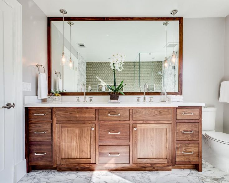 Soft+gray+walls+with+white+molding+create+a+perfect+color+scheme+to+compliment+the+marble+flooring+of+this+bright,+transitional+bathroom.+The+large+wood+vanity+base+and+matching+mirror+frame+add+a+warmth+to+the+design.+Matching+pendant+lights+hang+over+the+his+and+hers+sinks+built+into+the+white+countertop.