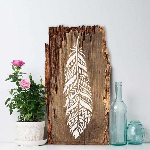 Tribal Feather Wall Art Stencil from Cutting Edge Stencils stenciled in white on a piece of driftwood. http://www.cuttingedgestencils.com/tribal-feather-stencil-ornate-feathers-stencils-design.html