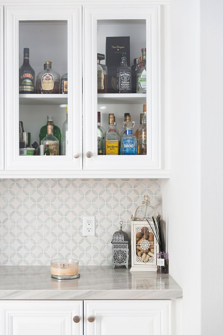 Marble Countertops Mingle With A White Pearl Tile Backsplash.